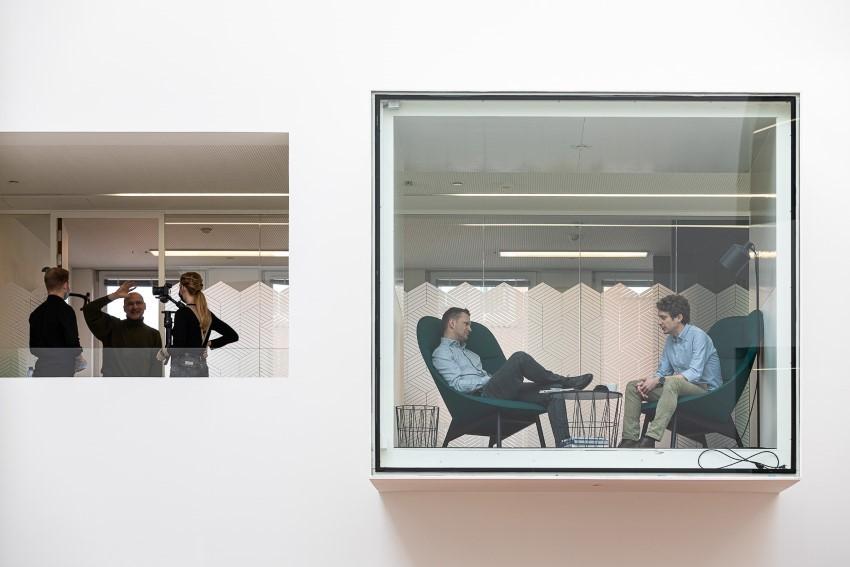 Mensen van Oxygen achter een raam, in bespreking